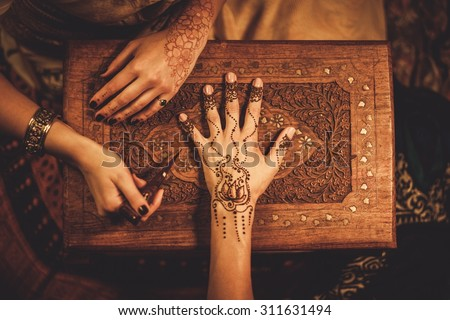 Drawing process of henna menhdi ornament on woman's hand  - stock photo