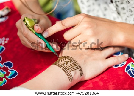 Drawing process of Henna or Menhdi ornament on woman's hand. It is prepared from the plant and to create the art of temporary body art or skin decoration called henna tattoos.