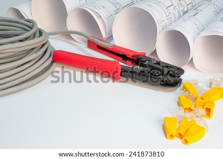 Drawing rolls, cat 5 cable, crimping pliers, connectors and boot caps - stock photo