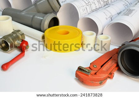 Drawing rolls, gas wrench, pipe joints, Y fitting, ball valve, drain pipe, plumber's tape - stock photo