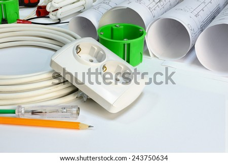 Drawing rolls, wall socket, socket box, power cable, screwdriver, lamp, test pen, pencil, fastener and wire connectors on white surface - stock photo