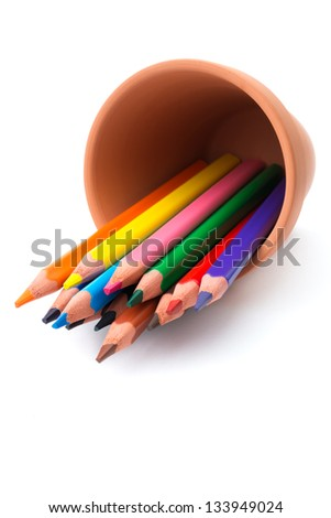 Drawing supplies: assorted color pencils in ceramic pot, isolated on white background - stock photo