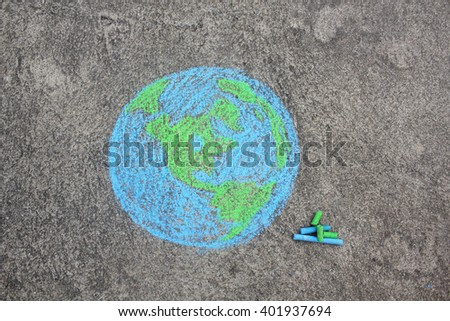 Drawing the world with chalk on the street floor. - stock photo