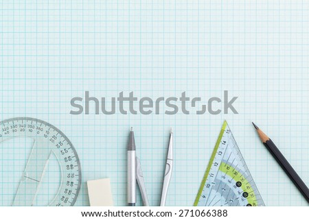 drawing tools on blue graph paper with copy space - stock photo