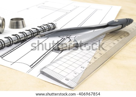 Drawings, and design tools on the table of an engineer or designer illustrating research and development process in engineering and technology.