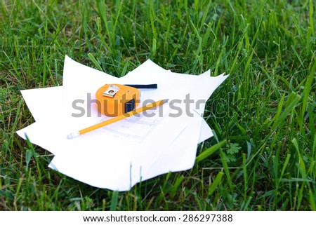 Drawings with pencil and roulette on green grass - stock photo