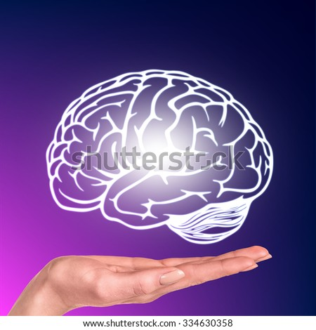 Drawn brain hovered over the human hand on the purple background - stock photo