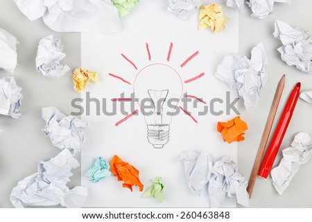 drawn lightbulb surrounded by crumpled pieces of paper - stock photo