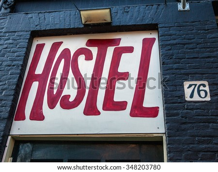 Drawn red hostel sign on old building in downtown. - stock photo