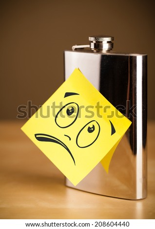 Drawn smiley face on a note stuck on a hip flask - stock photo