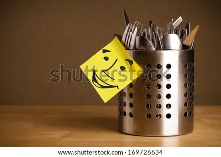 Drawn smiley face on a post-it note sticked on a cutlery case - stock photo