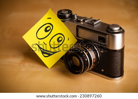Drawn smiley face on a post-it note sticked on a photo camera - stock photo