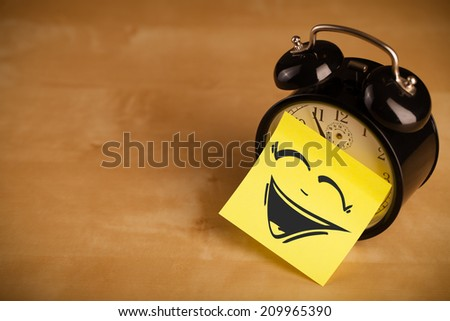 Drawn smiley face on a post-it note sticked on alarm clock - stock photo