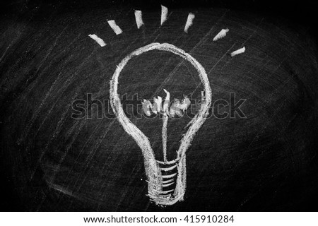 draws a chalk lightbulb on a black board - stock photo