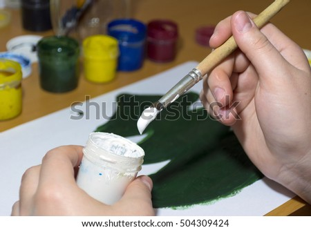 draws green tree gouache, scoops the white paint from the jar with a brush, hands, drawing