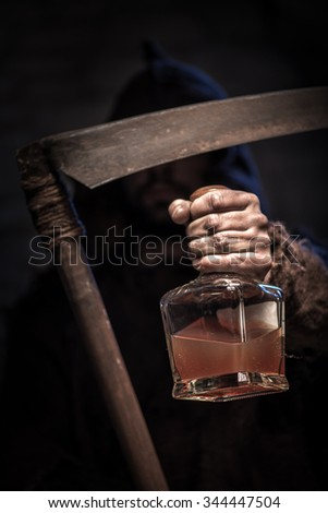 Dreadful death character is holding a scythe. He is stretching forward the bottle of alcohol drink with threats - stock photo