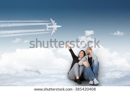 Dream about traveling. Two people dream of a wonderful vacation sitting in the clouds and show the plane. - stock photo