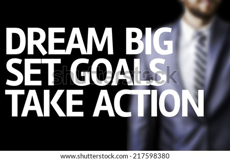 Dream Big Set Goals Take Action written on a board with a business man on background - stock photo