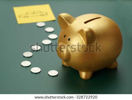Dream car savings - golden piggy bank, coins and a car sketch - stock photo