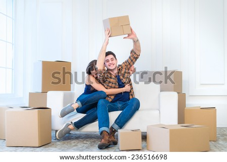 Dream come true, moving. Loving couple enjoys a new apartment and keep the box in his hands while young and beautiful couple in love sitting on the couch in an empty apartment among boxes