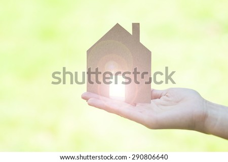 dream house in a female hand, light blurs coming through - stock photo
