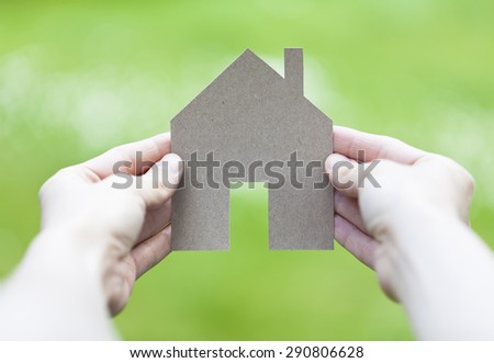 dream house in women's hands with green background - stock photo