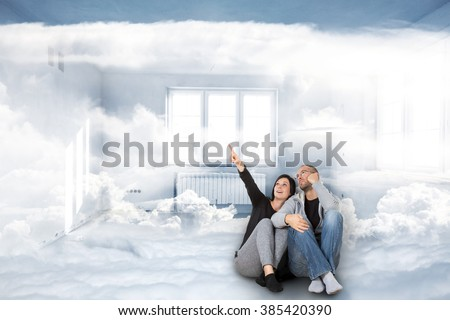 Dream of a new home. Two people are dreaming about a new home sitting in the clouds. - stock photo