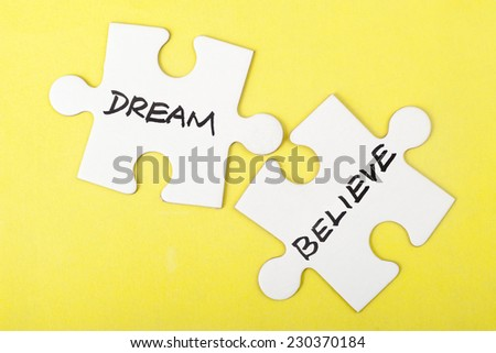 Dream or believe words on two pieces of jigsaw puzzle - stock photo