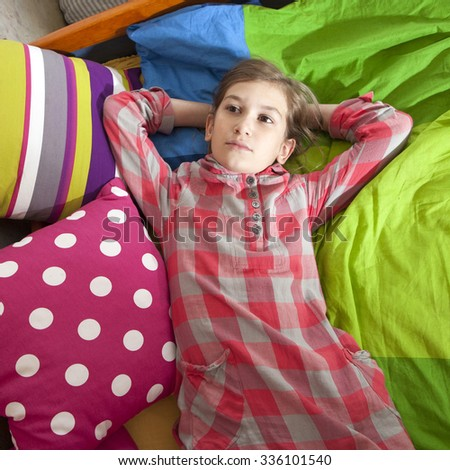 dreamer girl eleven years old lying on the bed between color pillow - stock photo