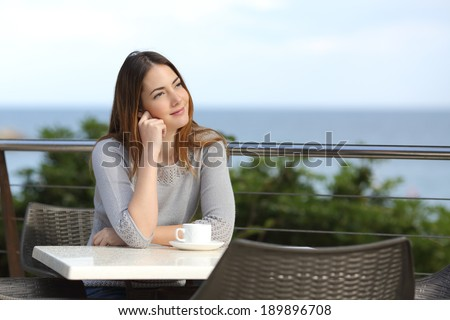 Dreamer woman pensive sitting in a terrace of a restaurant with the beach in the background - stock photo