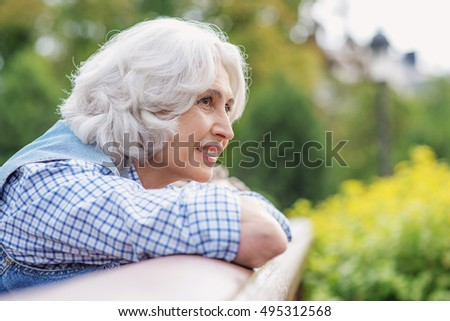 Dreamful old lady relaxing outdoors