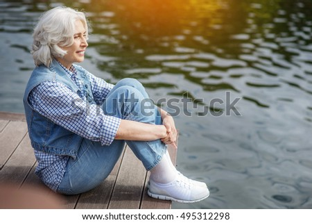 Dreamful old lady resting near water