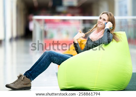 Dreamily smiling young woman in casual style clothes sitting on bean bag in contemporary interior, recreational area, using smartphone, talking, making call, waiting for meeting - stock photo