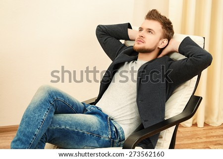 Dreamily thoughtful young man sitting relaxed on the armchair. - stock photo
