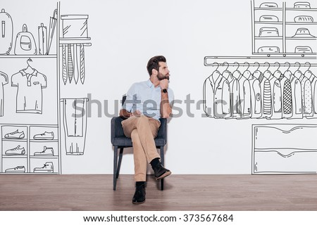 Dreaming about new wardrobe. Young handsome man keeping hand on chin and looking away while sitting in the chair against illustration of closet in the background - stock photo