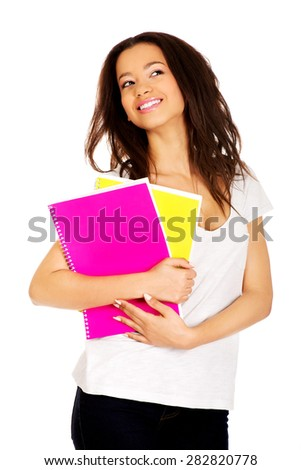 Dreaming african student woman with notes. - stock photo