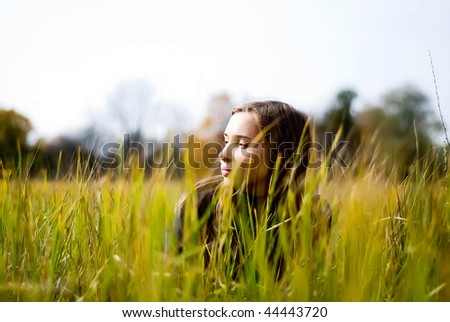 dreaming beautiful girl lying in a meadow. view through the grass