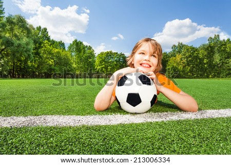 Dreaming boy holds football, looking and laying
