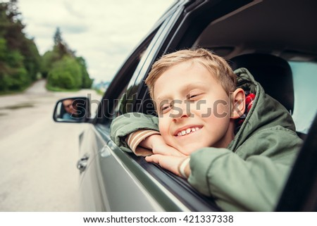 Dreaming boy look out from the car window - stock photo