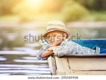 Dreaming boy lying in old boat on the river - stock photo