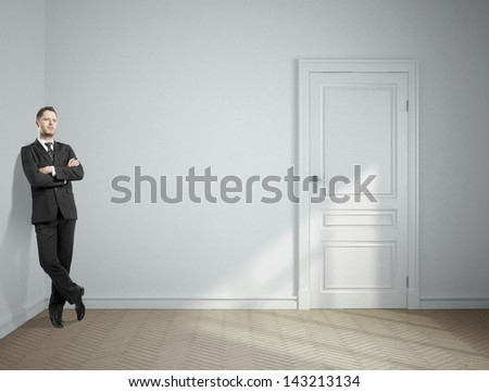dreaming businessman standing in gray room - stock photo