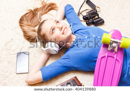 Dreaming cheerful teenage girl lying on the floor with penny board camera phone binoculars. Happy teenager girl dreaming about travelling - stock photo