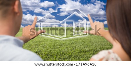 Dreaming Couple Framing Hands Around Ghosted House Figure in Grass Field. - stock photo