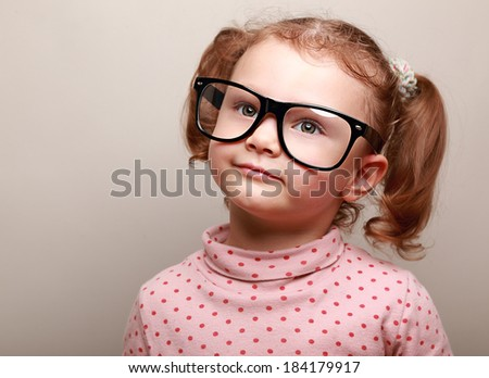 Dreaming cute girl in glasses looking up on copy space