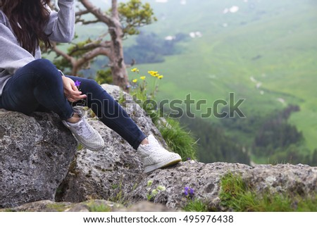 Dreaming girl sits on the edge of the cliff and looking at the sun valley and mountains