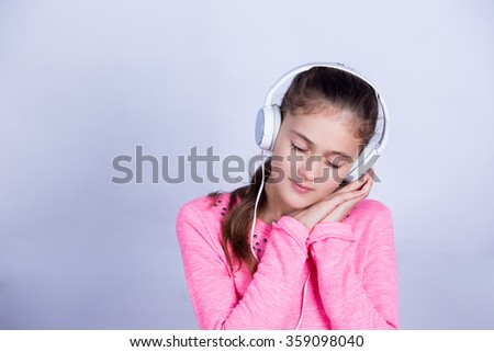 Dreaming Little girl enjoying music in headphones at home relaxing. Relaxed little girl listening to music with earphones  looking serene and happy. - stock photo