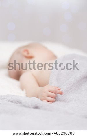 Dreaming newborn baby covered by gentle blanket in bright interior