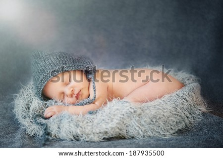 Dreaming Newborn Baby - naked in Hat on soft Grey  Blanket - stock photo