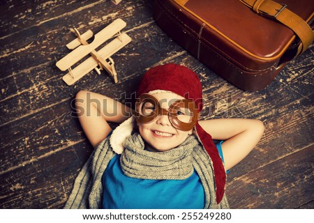 Dreaming of a big sky. Top view of happy little boy in pilot headwear and eyeglasses lying on the hardwood floor and smiling while wooden planer and briefcase laying near him  - stock photo