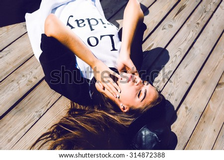 Dreaming of a big trip. Top view of beautiful young woman in eyewear lying on the hardwood floor and smiling while suitcase and camera laying near her.Sweater warm,vintage colors,dreaming girl,hipster - stock photo